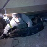 Shane installing vapor barrier in a crawlspace