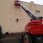 Using man lift to install exterior exhaust pipe